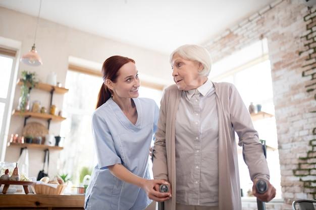 Rothaarige weibliche pflegekraft, die frau mit krücken unterstützt Premium Fotos