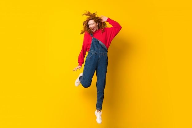 Rothaarigefrau mit dem overall, der über lokalisierte gelbe wand springt Premium Fotos