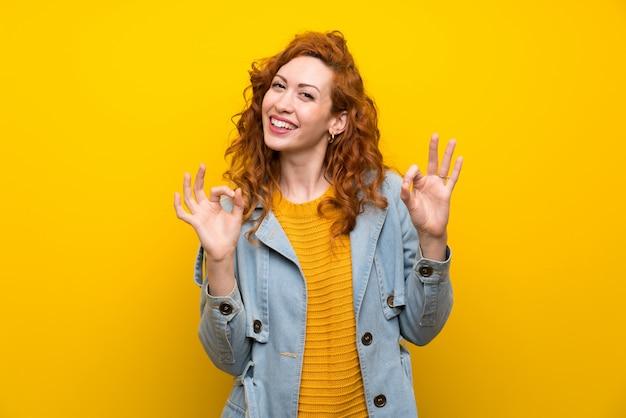 Rothaarigefrau über dem lokalisierten gelb, das ein okayzeichen mit den fingern zeigt Premium Fotos