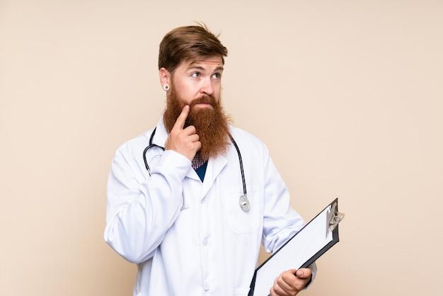 Rothaarigemann mit langem bart mit doktorkleid und halten eines ordners beim denken Premium Fotos