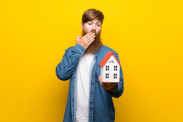 Rothaarigemann mit langem bart über der lokalisierten gelben wand, die ein kleines haus hält Premium Fotos