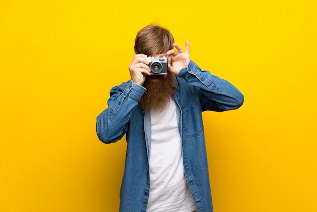 Rothaarigemann mit langem bart über der lokalisierten gelben wand, die eine kamera hält Premium Fotos
