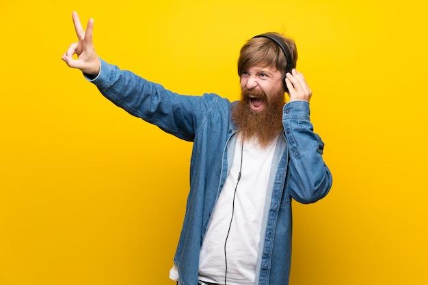 Rothaarigemann mit langem bart über lokalisierter gelber wand hörend musik mit kopfhörern Premium Fotos