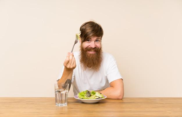Rothaariger mit langem bart und mit salat Premium Fotos