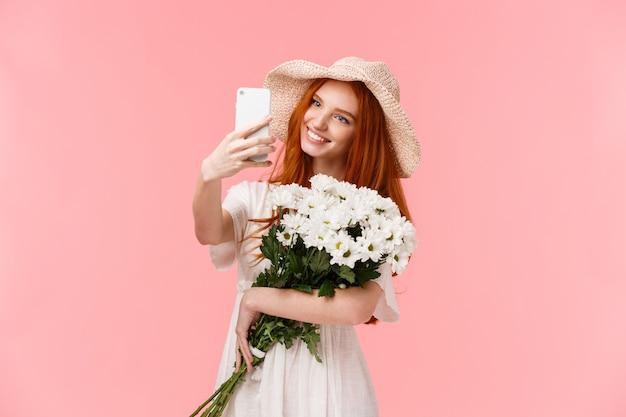 Rothaariges mädchen mit schönem blumenstrauß im weißen kleid, das selfie nimmt Premium Fotos