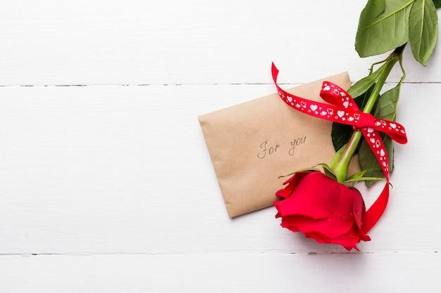 Rotrose, liebesmitteilung auf einem weißen hölzernen hintergrund Premium Fotos