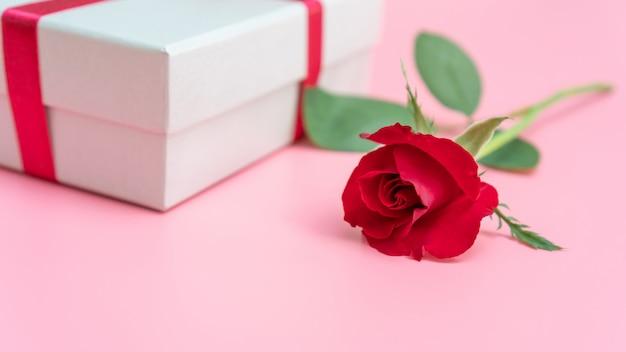Rotrose und geschenkbox auf einem rosa hintergrund. Premium Fotos