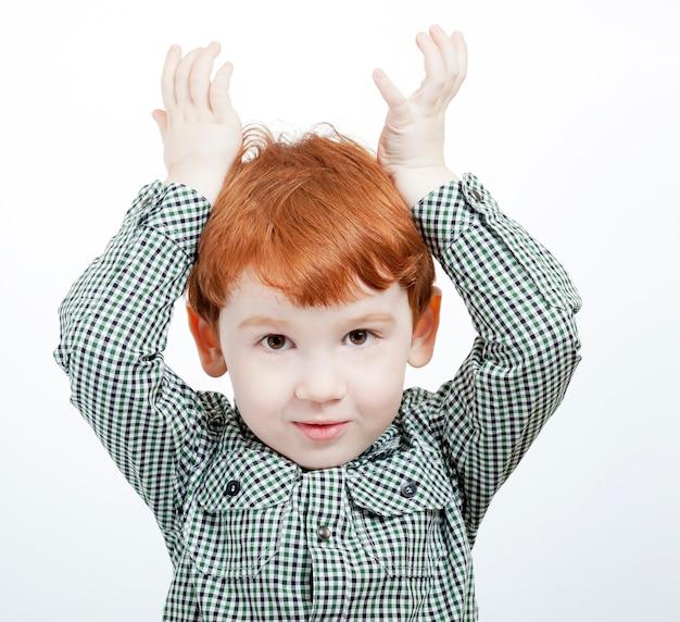 Rotschopf kleiner junge spielt mit seinen händen und hält sie über den kopf wie die hörner eines wilden tieres, nahaufnahme auf einer hellen oberfläche, nicht isoliert Premium Fotos