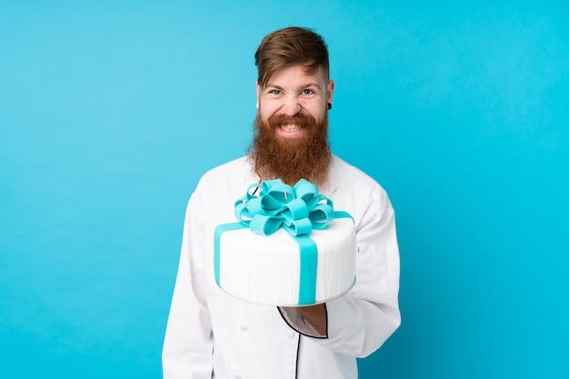 Rotschopf-konditor mit langem bart, der einen großen kuchen über isolierter blauer wand hält Premium Fotos