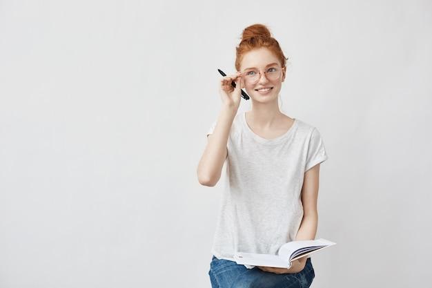 Rotschopf studentin lächelnd korrigierende brille hält notizbuch. Kostenlose Fotos