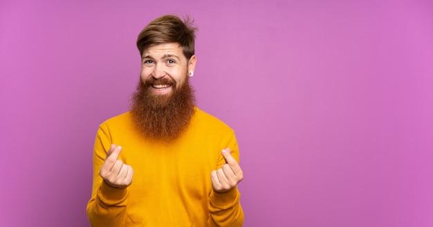 Rotschopfmann mit langem bart über isoliertem purpur, der geldgeste macht Premium Fotos