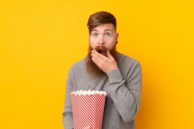 Rotschopfmann mit langem bart über isolierter gelber wand, die einen großen eimer popcorns hält Premium Fotos