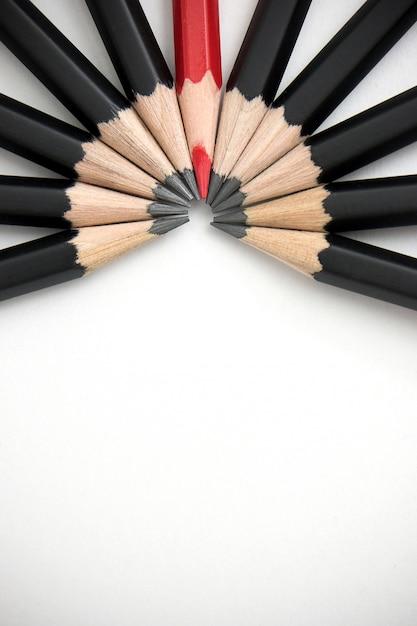 Rotstift, der heraus von der menge von viel identischen schwarzen gefährten auf weißer tabelle steht. Premium Fotos