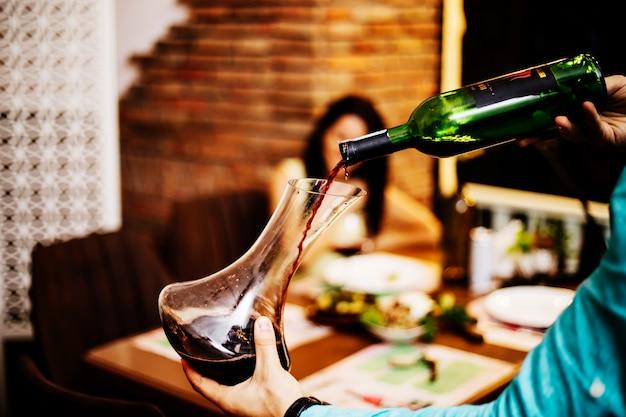 Rotwein aus der flasche in ein glas geben. Kostenlose Fotos