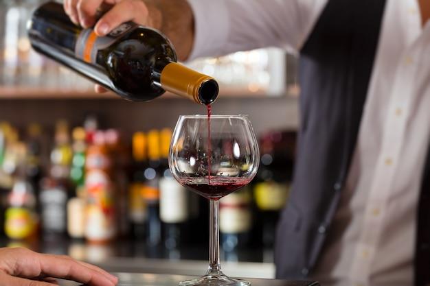 Rotwein, der in glas an der bar gießt Premium Fotos