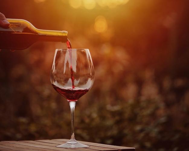 Rotwein gießen. weinglas rotwein im dorf bei sonnenuntergang. Premium Fotos