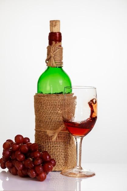 Rotwein im glas mit trauben und flasche auf weißem hintergrund. Premium Fotos