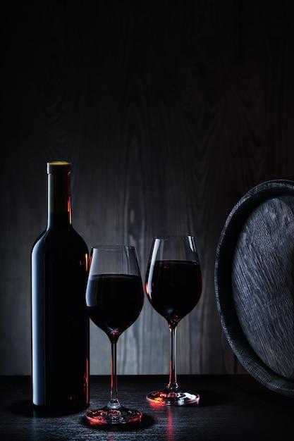 Rotwein im glas und in der flasche auf hintergrund von hölzernen fässern und von wänden Premium Fotos