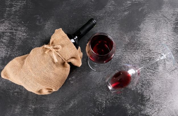 Rotweinflasche der seitenansicht in sackleinenbeutel auf schwarzem stein horizontal Kostenlose Fotos