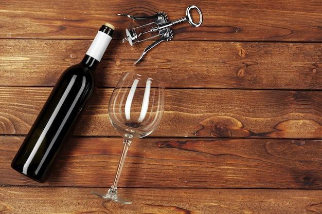 Rotweinflasche, weinglas und korkenzieher auf holztischhintergrund Premium Fotos