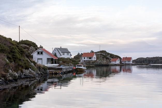 Rovaer in haugesund, norwegen - 11. januar 2018: der rovaer-archipel in haugesund, in der norwegischen westküste. pier und fischerboot, häuser am meer. Premium Fotos