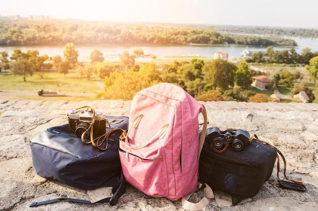Rucksack; kamera und fernglas auf dem boden im freien Kostenlose Fotos