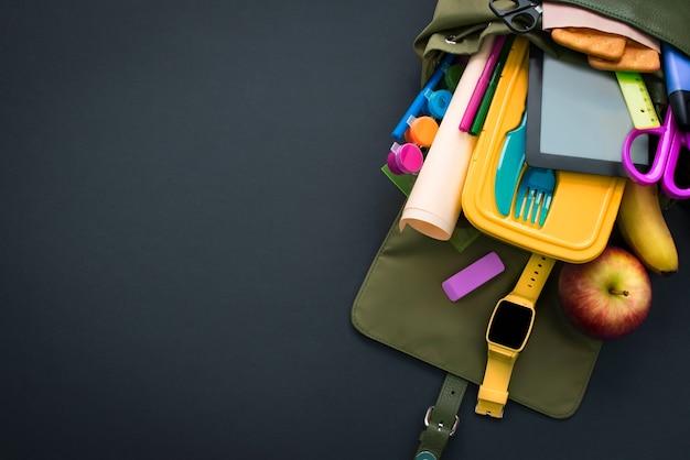 Rucksack mit schulmaterial auf schwarzem hintergrund. Premium Fotos