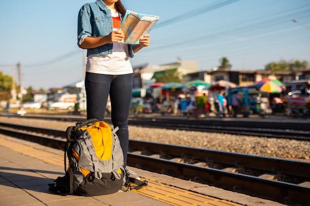 Rucksack und asiatische frau, die karte am bahnhof mit einem reisenden halten. reise-konzept. Premium Fotos
