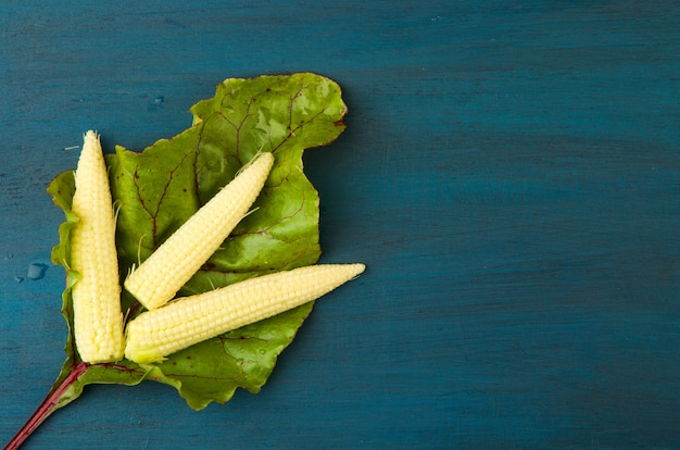 Rübenblatt frischer roher mais unter der hellen holzoberfläche. Premium Fotos