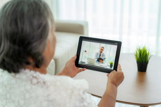Rückansicht der älteren frau, die videoanruf mit ihrem arzt mit ihrem übelkeitsgefühl auf digitaler tablet-online-gesundheitsberatung für digitale technologie macht, während sie zu hause bleibt. Premium Fotos