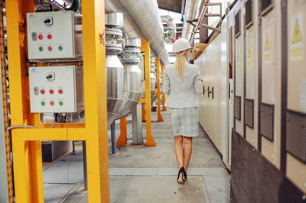 Rückansicht der blonden geschäftsfrau im anzug, mit schutzmaske, mit helm auf kopf, der durch heizwerk geht. Premium Fotos