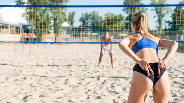 Rückansicht der frau, die teamkollegen mit den händen beim spielen des volleyball signalisiert Kostenlose Fotos