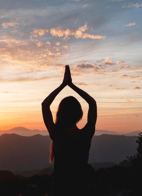 Rückansicht der frau in der yoga-pose während des sonnenuntergangs Kostenlose Fotos
