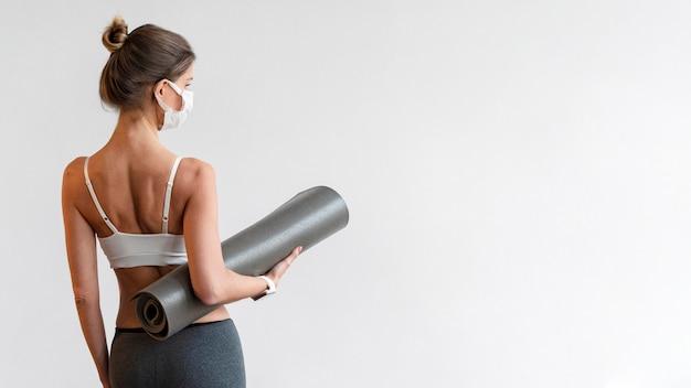 Rückansicht der frau mit der medizinischen maske, die yogamatte hält Kostenlose Fotos