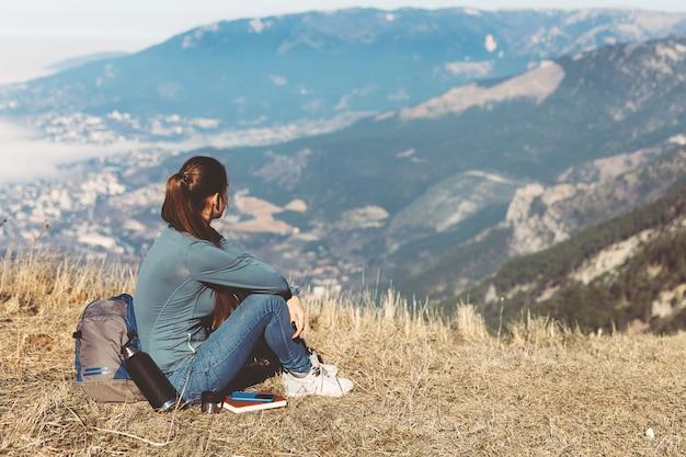 Rückansicht der frauenreise. junges schönes mädchen reist allein in den bergen im frühling oder herbst, sitzt am rande des berges und schaut in die ferne Premium Fotos