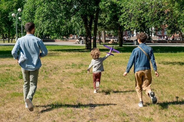 Rückansicht der glücklichen jungen familie der eltern und ihres niedlichen kleinen sohnes mit spielzeug, das grünen rasen hinunter läuft, während spaß im öffentlichen park hat Premium Fotos