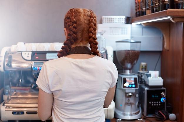 Rückansicht der kellnerin, die bestellung von ihrem kunden im café macht. kellnerin posiert rückwärts Premium Fotos
