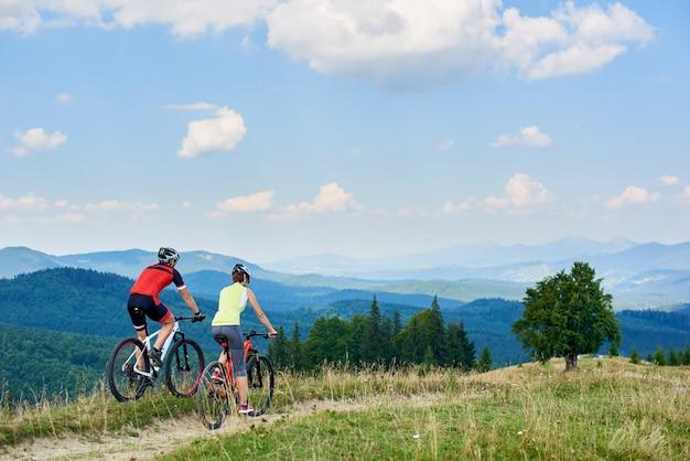 Rückansicht der radfahrer des athletenpaares, die langlaufräder auf bergpfad am sommertag radeln Premium Fotos