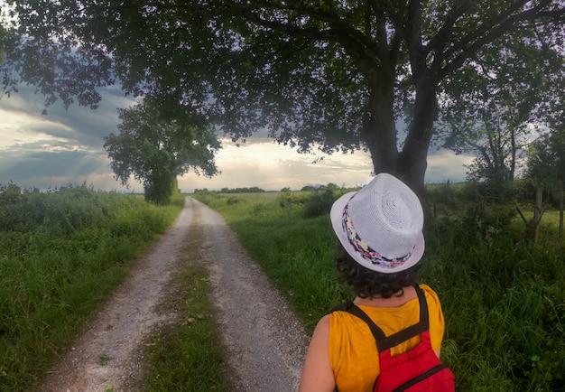 Rückansicht der wandernden frau mit sommerhut Premium Fotos