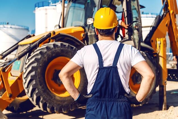 Rückansicht des arbeiters in uniform, der bagger beim stehen in der raffinerie betrachtet. Premium Fotos