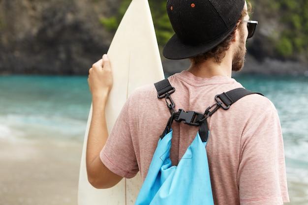 Rückansicht des jungen bärtigen anfängersurfers, der hysterese, sonnenbrille und blaue tasche auf seiner schulter trägt, weißes surfbrett hält und azurblaues meerwasser betrachtet Kostenlose Fotos