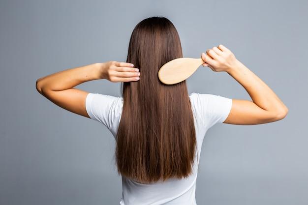 Rückansicht des kämmens des gesunden langen geraden weiblichen haares lokalisiert auf grau Kostenlose Fotos