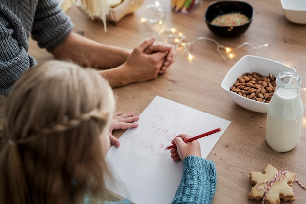 Rückansicht des mädchens, das einen brief an den weihnachtsmann schreibt Kostenlose Fotos