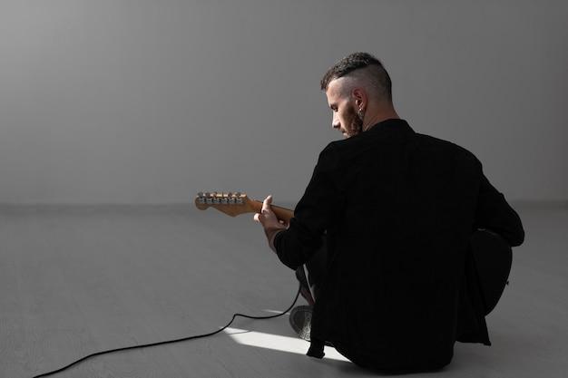 Rückansicht des männlichen künstlers, der e-gitarre spielt Kostenlose Fotos