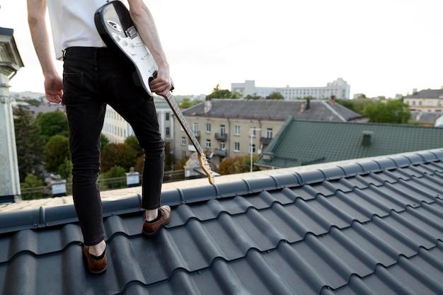 Rückansicht des männlichen musikers auf dach, der e-gitarre hält Kostenlose Fotos