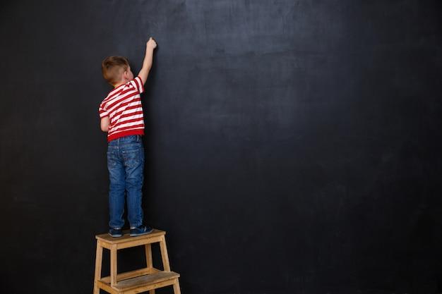 Rückansicht des niedlichen kleinen jungen, der mit kreide schreibt Kostenlose Fotos