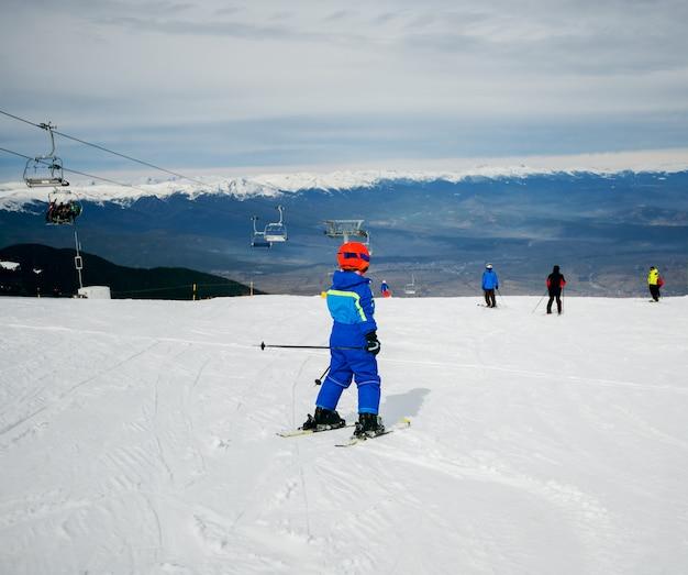 Rückansicht des skifahrens des kleinen kindes in den bergen mit sicherheitsausrüstung. Premium Fotos