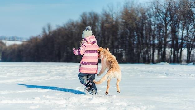 Rückansicht des verspielten hundes und des reizenden mädchens draußen im winter Premium Fotos