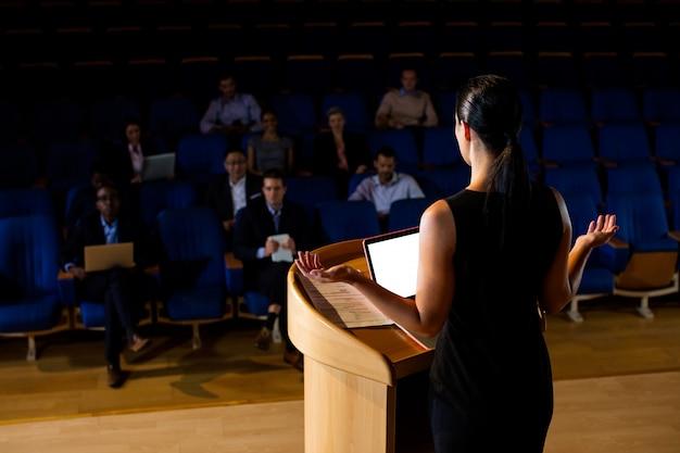 Rückansicht des weiblichen geschäftsführers, der eine rede hält Kostenlose Fotos