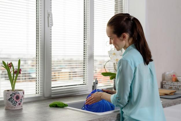 Rückansicht einer frau beim abwasch in der küche vor dem fenster Premium Fotos